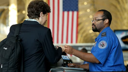 An officer from the Transportation Security Administration checks travel documents for passengers traveling through Reagan National Airport.