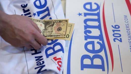 A campaign volunteer for Bernie Sanders, handles contribution money from a supporter.