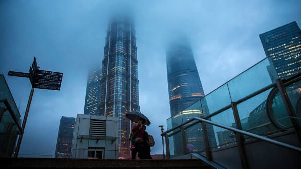 Pedestrians holding an umbrella walk as buildings stand shrouded in haze in the Lujiazui district of Shanghai, China.