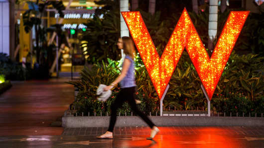 A woman walks past signage displayed outside of the W Hotel Hollywood in Hollywood, California.