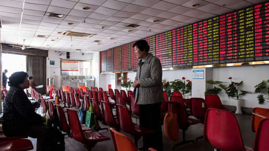 Investors chat while standing next to an electric board showing stock market movements at a securities brokerage in Shanghai.