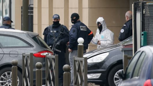 French Police and a forensic expert stand at the entrance of an apartment building after a raid in Argenteuil, a suburb in northern Paris, France, March 25, 2016 following the arrest of a French national suspected of belonging to a militant network planning an attack in France.