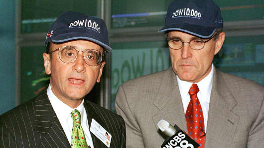 New York Stock Exchange Chairman Richard Grasso (L) and New York City Mayor Rudy Giuliani (R) wear 'Dow 10,000' hats on March 29, 1999.