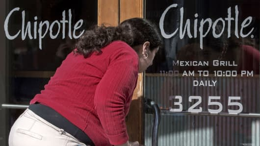 A woman looks through the locked front door of the Chipolte Restaurant in Washington, D.C.
