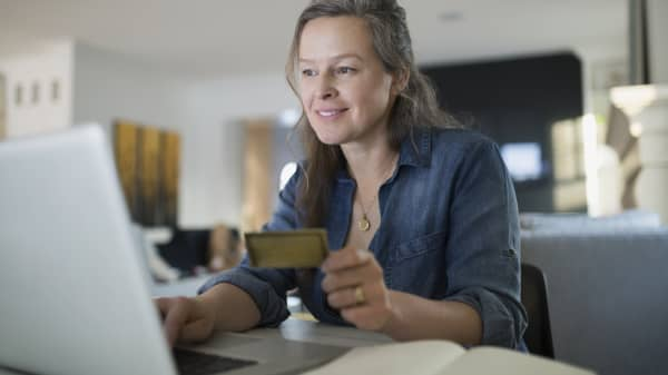 Woman with credit card online shopping with laptop