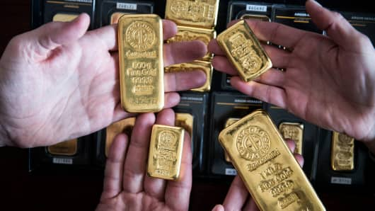 Employees hold mixed-weight Argor-Heraeus SA branded gold bars in this arranged photograph at Solar Capital Gold Zrt. in Budapest, Hungary.
