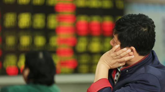 An investor observes stock market at an exchange hall in Haikou, Hainan Province of China.