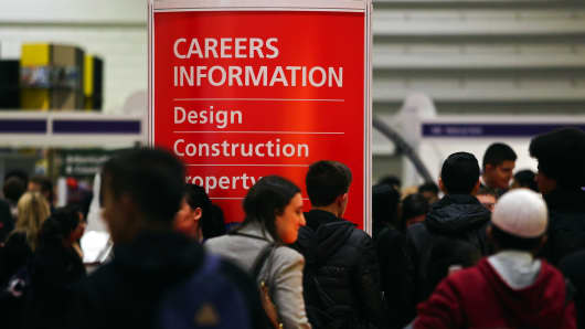 Visitors walk past a Careers Information display board as they pass job exhibition booths at a job fair