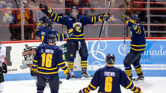 Scott Davidson #22 of the Quinnipiac University Bobcats celebrates his first-period goal against the Northeastern Huskies with his teammate Sam Anas #7 and Alex Miner-Barron #8 during an NCAA hockey game at Matthews Arena on Jan. 2, 2016 in Boston.