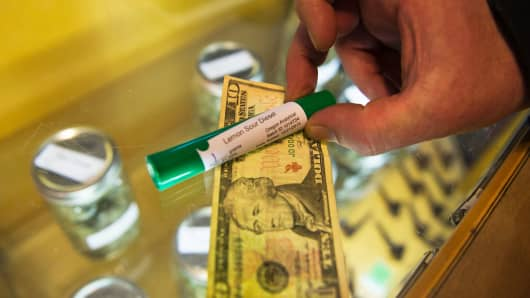 A customer buys a marijuana joint at a dispensary in Eugene, Oregon on March 22, 2016.