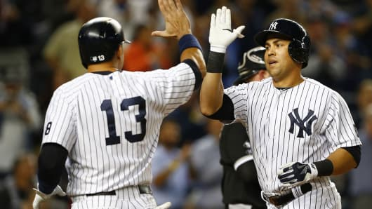 Carlos Beltran of the New York Yankees is congratulated by teammate Alex Rodriguez after hitting a three-run home run against the Chicago White Sox.