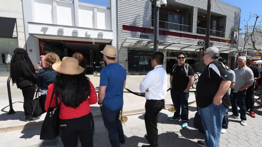 Customers wait in line to put a USD 1,000 deposit on the as yet unseen Tesla Model 3, outside the Tesla store on the Third Street Promenade in Santa Monica, California, on March 31, 2016.