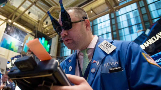 A trader wearing novelty glasses in the shape of champagne bottles works at the New York Stock Exchange (NYSE) in New York.
