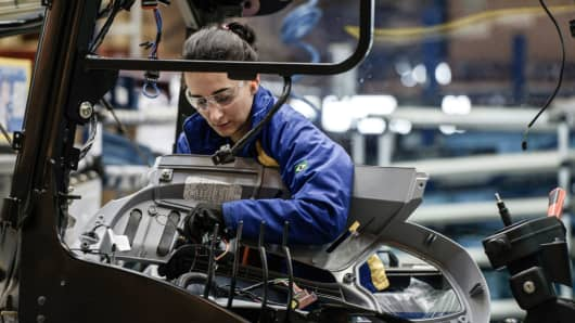 A worker checks a tractor on the assembly line at the Case New Holland factory in Curitiba, Brazil.