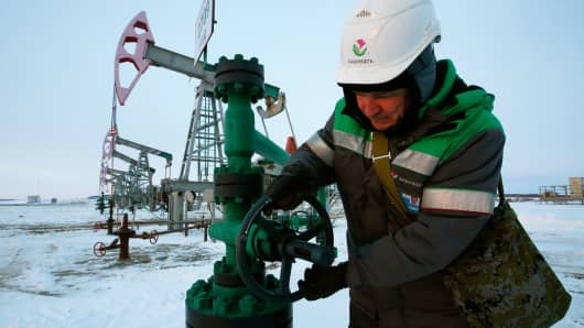 A worker checks the valve of an oil pipe at an oil field owned by Bashneft company near Nikolo-Berezovka, Bashkortostan, Russia.