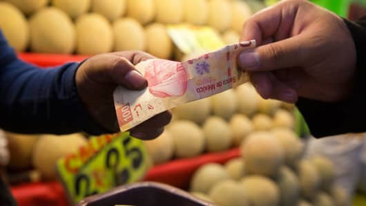 A shopper pays for pears with a 100-peso bill at a fruit stand in Mexico City.