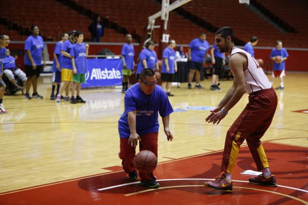 Sam Dhillon #13 from the USC Trojans plays a basketball game with Special Olympics kids.