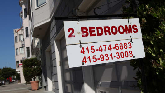 A sign advertising an apartment for rent is displayed in front of an apartment building in San Francisco, California.