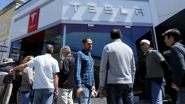 People wait in line at a Tesla Motors dealership to place deposits on the electric car company's mid-priced Model 3 in La Jolla, California, March 31, 2016.