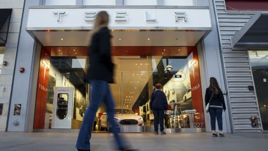 Pedestrians walk past the Tesla Motors Inc. store