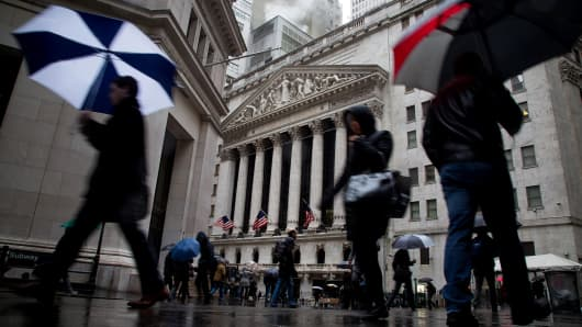 Pedestrians carry umbrellas while walking past the New York Stock Exchange (NYSE) in New York.