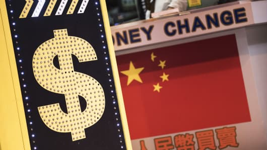 A sign displaying the Hong Kong dollar and Chinese yuan currency signs sits outside a currency exchange store in Hong Kong, China.