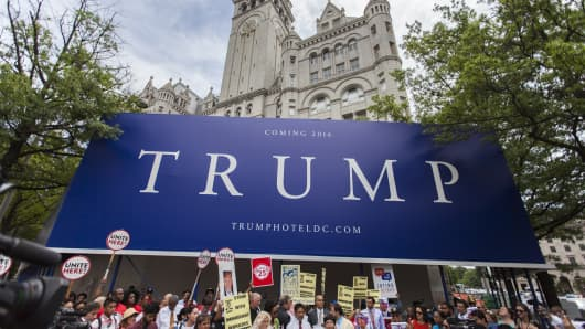 People gather in front of the under construction Trump Hotel to protest Donald Trump