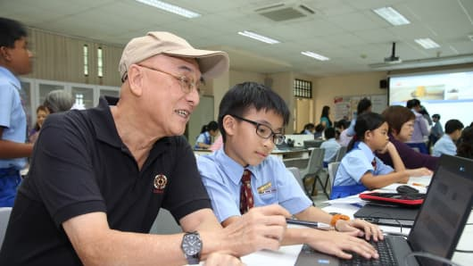 A senior participant learns from his 10-year old cyberguide at the North East Eldersurf Intergen Bootcamp, Singapore.