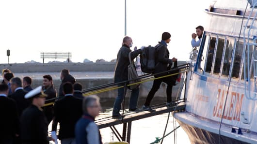 Frontex police escort migrants, who are being deported from Lesbos, onto a ferry before it returns to Turkey on April 4, 2016, in Lesbos, Greece.
