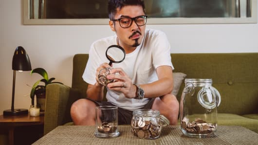 Man examining coins with magnifying glass  at home
