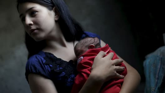 Ianka Mikaelle Barbosa, 18, poses for a photograph with Sophia, 18 days old, who is her second child and was born with microcephaly, at her house in Campina Grande, Brazil February 17, 2016.