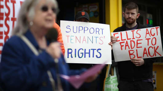 Activists and tenants of 1049 Market Street hold signs as they stage a protest against the landlord's attempts to evict them from the building on March 8, 2016 in San Francisco, California.