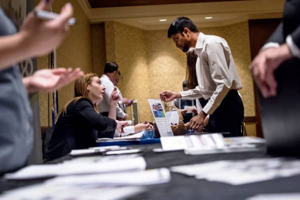 Job seekers, right, speak with recruiters at the San Jose Career Fair in San Jose, California.