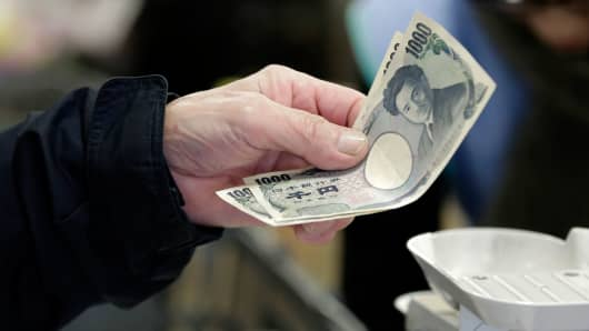 A customer hands over Japanese 1,000 yen banknotes while making a purchase at a supermarket in Tokyo.