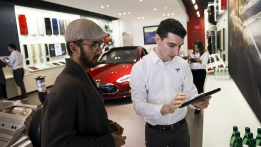 An employee assists a customer with pre-ordering the Tesla Motor Model 3 in Santa Monica, California, in March, 2016.