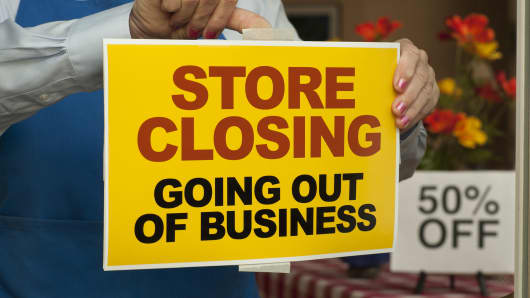 A store closing sign is taped on the door of a company going out of business.