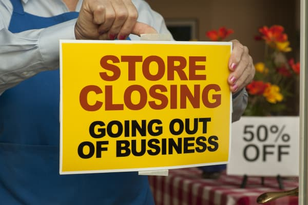 Store Closing sign being taped on door