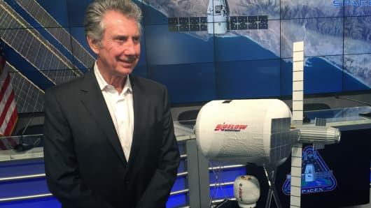 Robert Bigelow, founder of Bigelow Aerospace standing near a model of BEAM capsule.