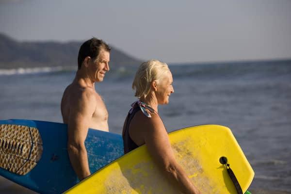 Retirement couple on beach surfing