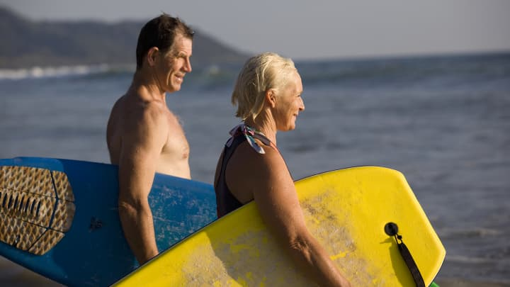 Retirement couple on beach surfing