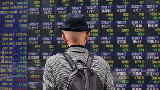 A pedestrian looks at a share prices board of the Tokyo Stock Exchange in Tokyo, Japan.