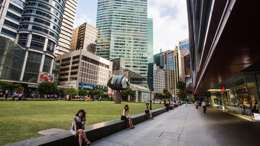 Women sit on a wall using mobile phones at Raffles Place in the central business district area of Singapore.