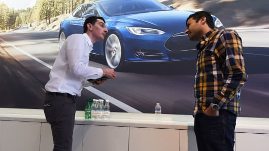 A salesperson (L) helps a customer pre-order the Tesla Model 3, in the Tesla store on the Third Street Promenade in Santa Monica, California, on March 31, 2016.