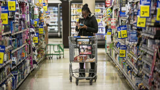 A woman checks a mobile phone while shopping at a Kroger grocery store in Birmingham, Mich.