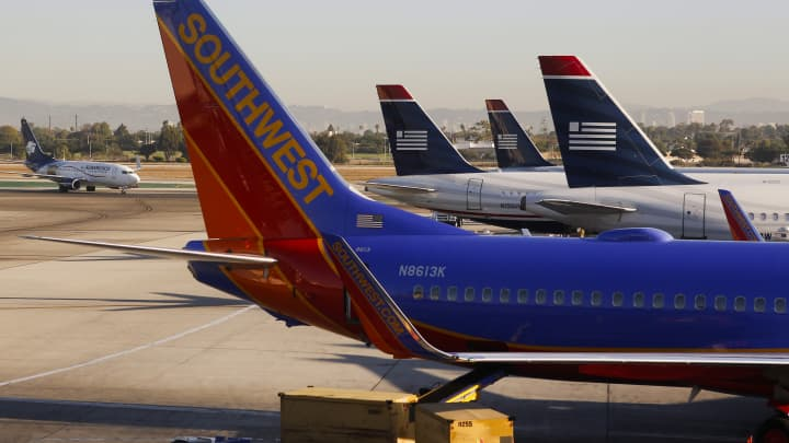 A Southwest Airlines Co. Boeing Co. 737-8H4 plane sits next to US Airways Group Inc. jets on the tarmac at Los Angeles International Airport (LAX) in Los Angeles.