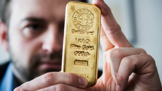 An Argor-Heraeus SA stamp sits on a one kilogram gold bar as an employee inspects it at Solar Capital Gold Zrt. in Budapest, Hungary