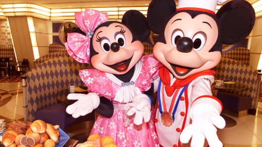 Mickey Mouse in chef's uniform, accompanied by Minnie Mouse, display a heap of breads on a plate