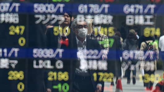 Pedestrians are reflected on an electronic stock quotation board at the window of a securities company in Tokyo.