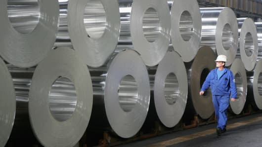 A worker walks among rolls of semi-finished aluminum at an Alcoa aluminum factory.