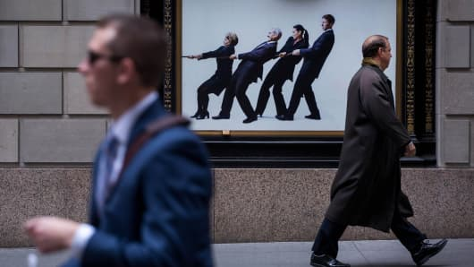 Pedestrians walk along Wall Street near the New York Stock Exchange (NYSE) in New York.